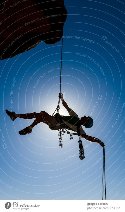 Climber on a free rappel. Human being Man Blue Adults Life Rock Masculine Success Adventure Rope Uniqueness Peak Climbing Trust Brave Balance
