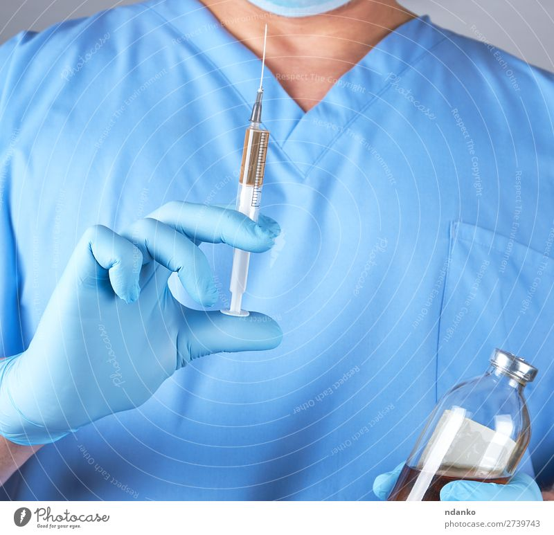 male doctor in blue uniform holding a syringe Health care Medical treatment Nursing Illness Medication Science & Research Laboratory Doctor Hospital Human being