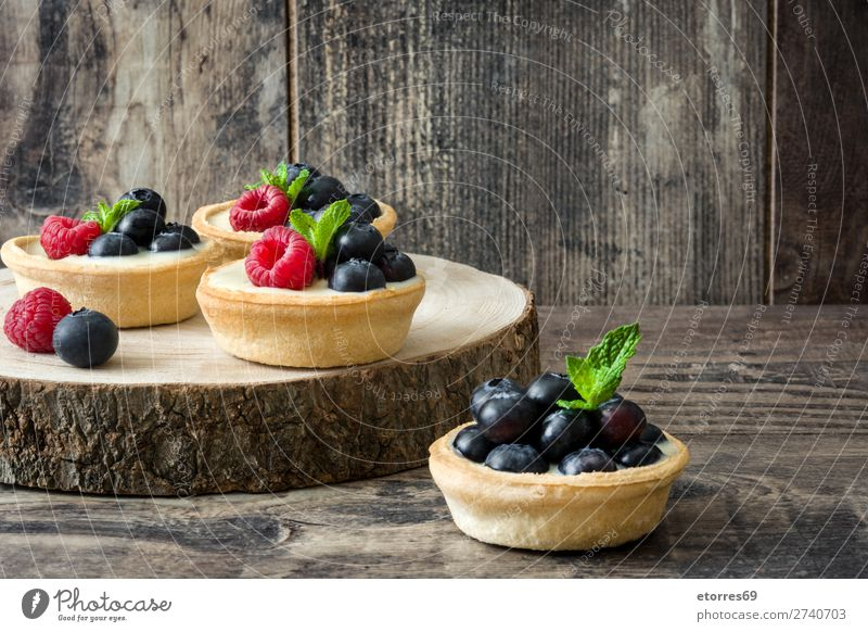 Delicious tartlets with raspberries and blueberries on trunk Tartlet Raspberry Blueberry Fruit Dessert Food Healthy Eating Food photograph Cream custard Snack