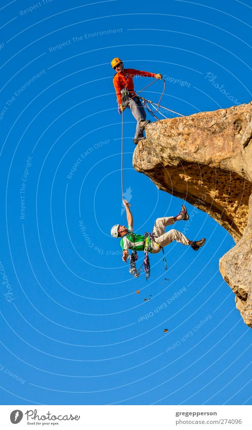 Climbing team in trouble. Human being Man Blue Adults Life Rock Power Masculine Dangerous Adventure Rope Help Peak To hold on To fall