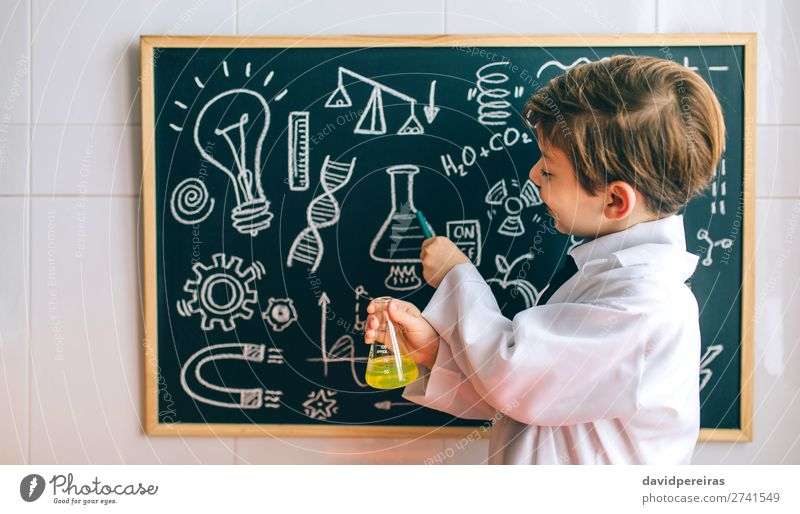 Boy dressed as chemist pointing at blackboard Happy Science & Research Child School Blackboard Laboratory Human being Boy (child) Man Adults Tie Blonde Smiling