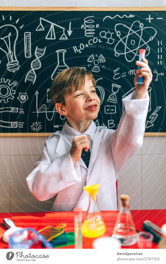 Boy playing with chemistry game Playing Science & Research Child Blackboard Laboratory Human being Boy (child) Man Adults Think Smart Considerate Chemist