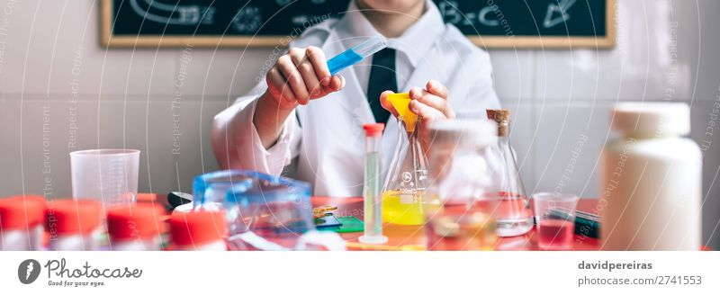 Serious little boy playing with chemical liquids Bottle Happy Playing Table Science & Research Child Classroom Blackboard Laboratory Internet Human being