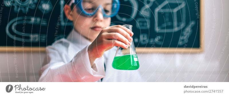 Serious boy holding flask with chemical liquid Bottle Playing Table Science & Research Child Classroom Blackboard Laboratory Internet Human being Boy (child)