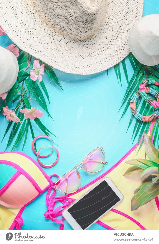 Top view of female beach accessories  background with tropical leaves and flowers , sunglasses and straw hat, bikini and smartphone on sunny blue. Summer holiday concept