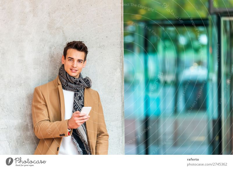 Young man wearing denim clothes leaning on a wall Lifestyle Elegant Style Beautiful Hair and hairstyles Telephone Cellphone PDA Human being Masculine