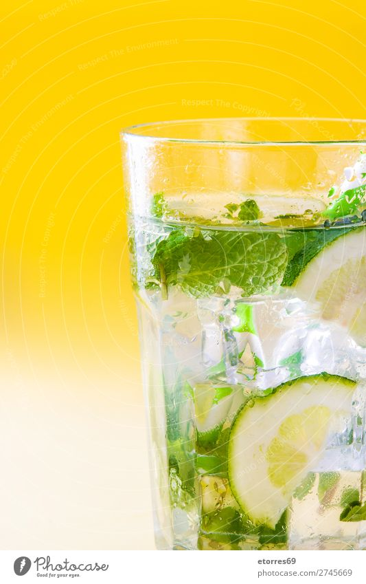 Mojito cocktail in glass on yellow background. Cocktail Beverage Drinking Alcoholic drinks Refreshment Summer Lime Green Mint Juice Rum Cold Ice Mixer Fruit