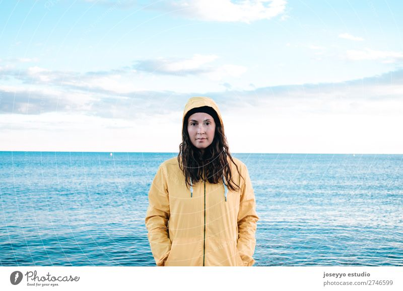 Woman on the beach with a yellow raincoat and hat Nature Sun Relaxation Winter Beach Lifestyle Adults Yellow Sports Coast Copy Space Freedom Fashion Trip
