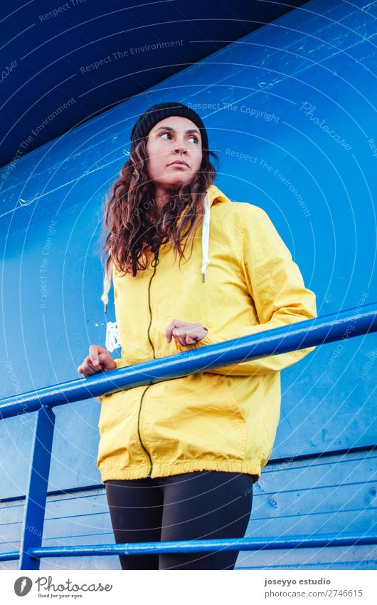 Young woman on a lifeguard tower Lifestyle Relaxation Trip Freedom Sun Beach Winter Sports Meeting 30 - 45 years Adults Nature Coast Fashion Jacket Hat Yellow