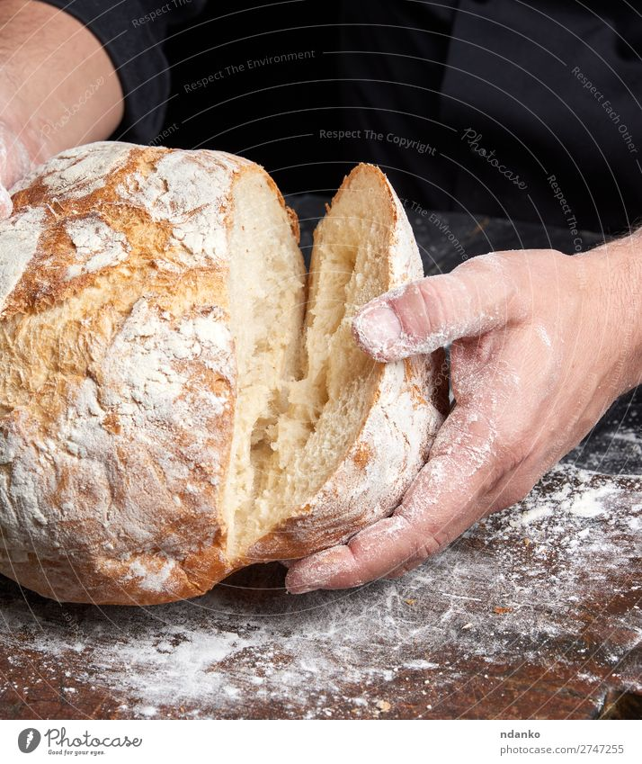 cook in a black tunic holds fresh baked bread Bread Nutrition Breakfast Table Kitchen Cook Human being Hand Fingers Wood Make Dark Fresh Brown Black White