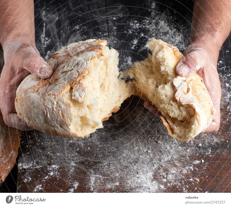 baked bread in half Bread Nutrition Table Kitchen Profession Cook Human being Hand Fingers Wood Make Dark Fresh Hot Brown Black White Tradition Baking Baker
