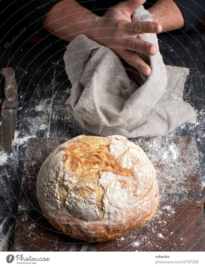 baked round bread on a board Bread Nutrition Table Kitchen Profession Cook Human being Hand Fingers Wood Make Dark Fresh Brown Black White Tradition chef Baking