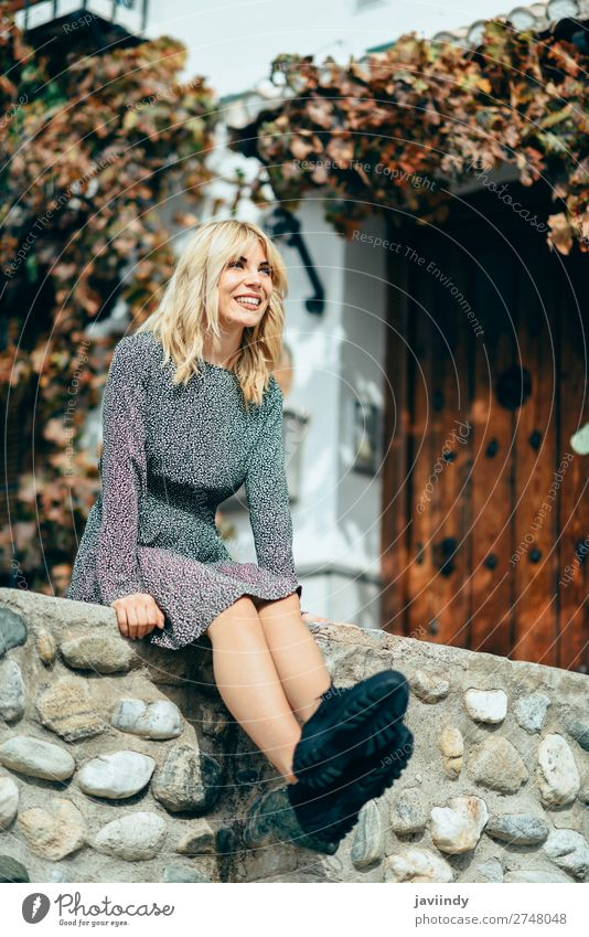 Happy young blond woman sitting on urban autumn background. Lifestyle Style Beautiful Hair and hairstyles Human being Feminine Young woman Youth (Young adults)