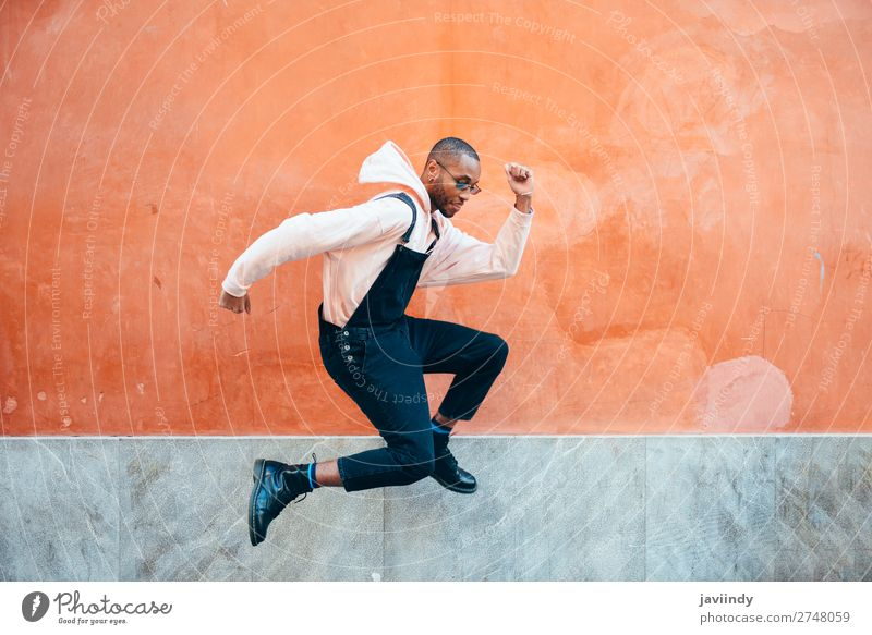 Young black man wearing casual clothes jumping outdoors Human being Youth (Young adults) Man Beautiful Young man Joy Black 18 - 30 years Street Lifestyle Adults