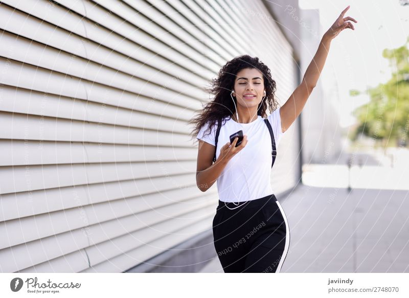 African woman listening to music with earphones and smartphone Style Joy Happy Beautiful Hair and hairstyles Music Sports Telephone PDA Technology Human being