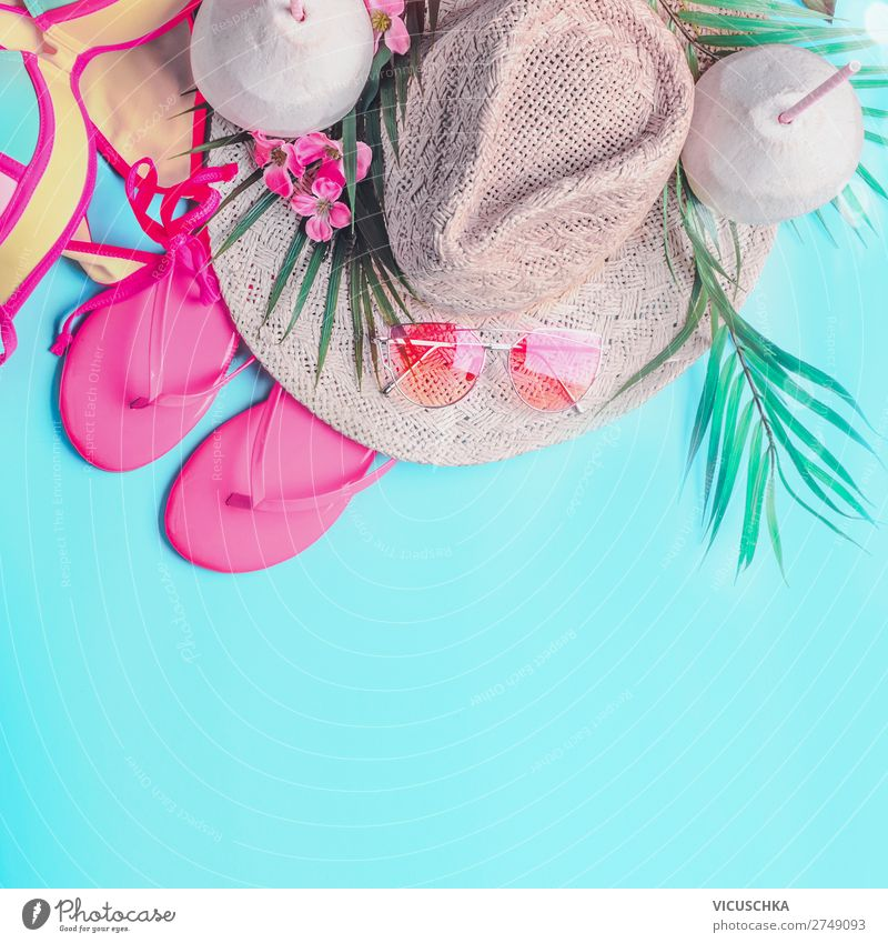 Summer background . Top view of woman's summer beach accessories: bikini,  flip flops, sunglasses, straw hat, palm leaves and tropical flowers on turquoise blue background, banner with copy space