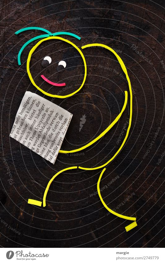Rubber worms: A man reads a newspaper with the text : Upcyceln Education Science & Research Study Academic studies Economy Human being Masculine Feminine