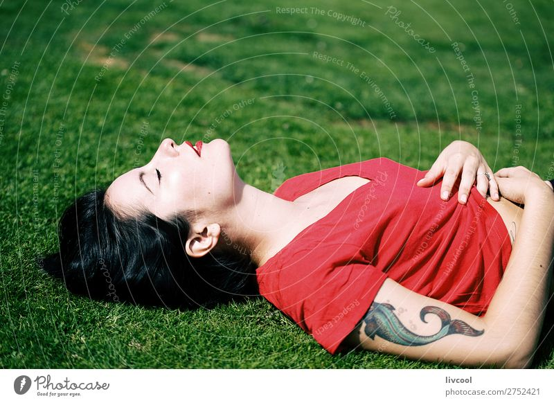 beautiful woman lying on the grass of a park Woman Human being Youth (Young adults) Young woman Summer Beautiful Green Red Hand Eroticism Relaxation Calm Black