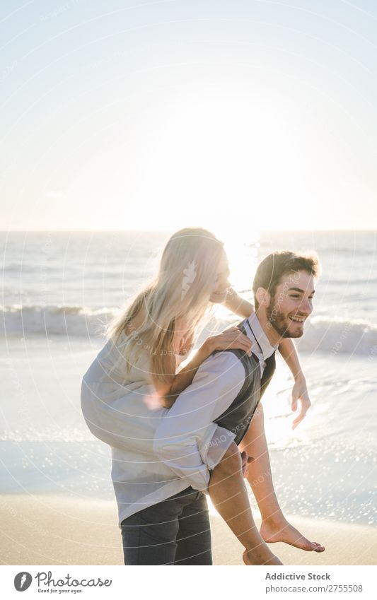Groom carrying charming girl on back Couple Wedding Beach Summer Ocean in love Bride Carrying Relaxation Laughter Cheerful Dress Beautiful Nature Engagement