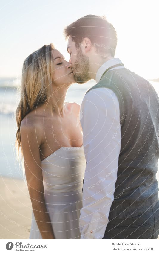 Tender kissing bridal couple in sunlight Couple Wedding Beach Sunlight Engagement Contentment Stand Relationship
