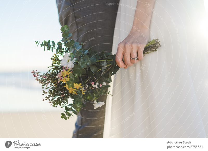 Crop bride with bouquet embracing groom Couple bridal Embrace Bouquet Feasts & Celebrations Wedding Nature romantic Beach Traveling Love Rustic Flower Together