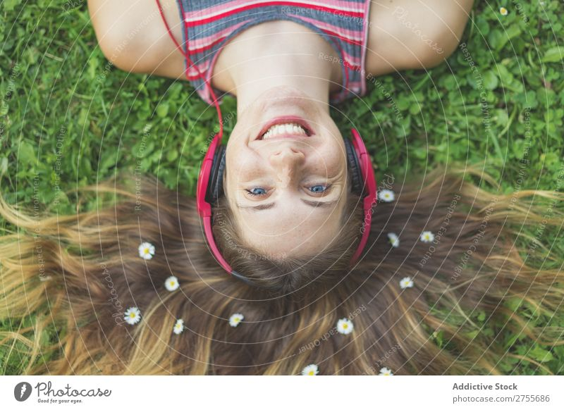 Excited girl in headphones on grass Woman Expressive Headphones Posture Grass Lie (Untruth) Park facial Flower Excitement Model Expression Style