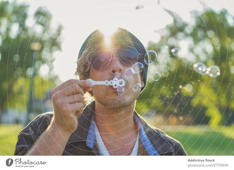 Man blowing soap bubbles in park Hipster Park Soap bubble romantic handsome Youth (Young adults) Playful Easygoing Modern Blow Posture Summer Playing Happiness