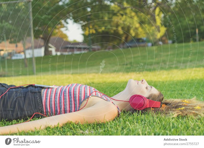 Girl with gadgets on lawn Woman Headphones Relaxation Feminine Music Dream Flower Meadow Entertainment Student Park Summer Freedom Contentment Nature Listening