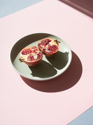 Halves of pomegranate in sunlight Pomegranate halves minimalist Mature Red Fruit Sweet Creativity Juicy section Organic Plate Shadow Multicoloured Arrangement