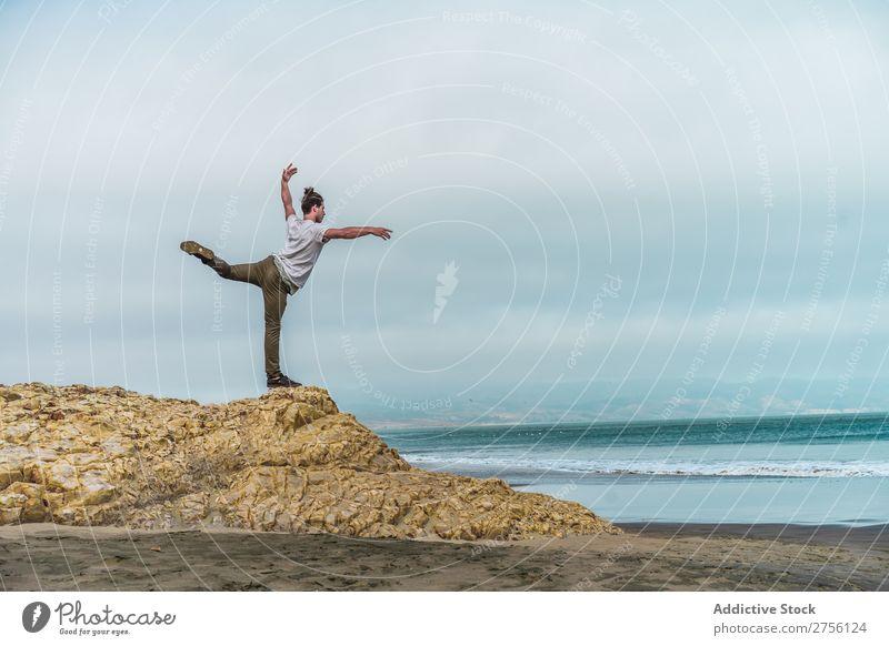 Man balancing on stone at sea Human being Coast Youth (Young adults) Ocean Balance Stone Yoga