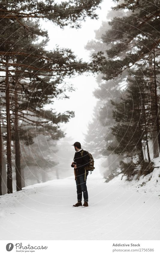 Tourist standing in snowy forest Man backpacker Street Stand Winter Forest Nature Snow Cold Frost Seasons Landscape White Beautiful Rural Looking back Frozen
