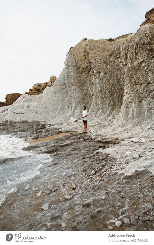 Man standing on rocky beach Tourist Cliff Ocean Rock Vacation & Travel Tourism Nature Landscape Coast Water Sun Freedom Stone Natural Lifestyle Beautiful