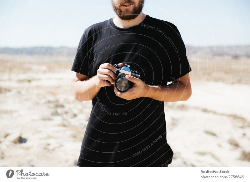 Crop man with camera on desert Man Hand Camera Illusion Trick Desert Vacation & Travel Lifestyle Human being Adults Nature Adventure Trip Hot Flying Tourist