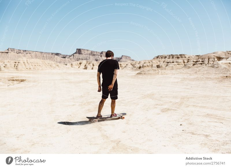 Man riding skateboard in desert Skateboard Desert Vacation & Travel Lifestyle Human being Adults Nature Adventure Trip Tourist Sports Action Extreme Cliff Hill