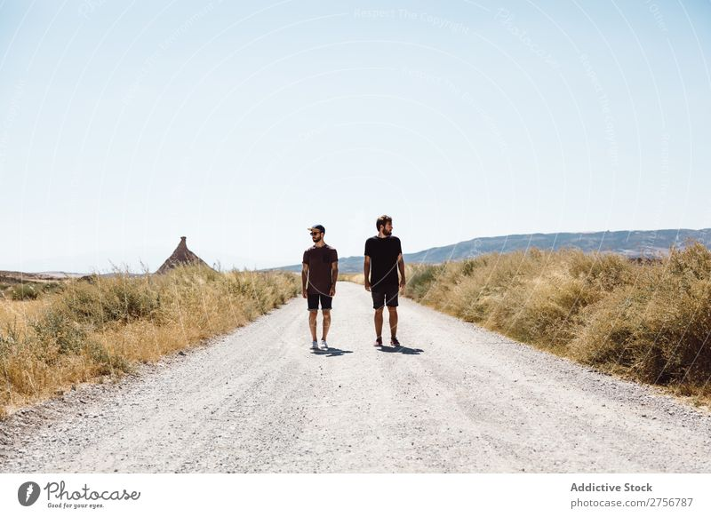 Two men walking along road Man prairie Street Vacation & Travel Lifestyle Human being Adults Nature Adventure Trip Tourist Landscape Grass Vantage point Sky