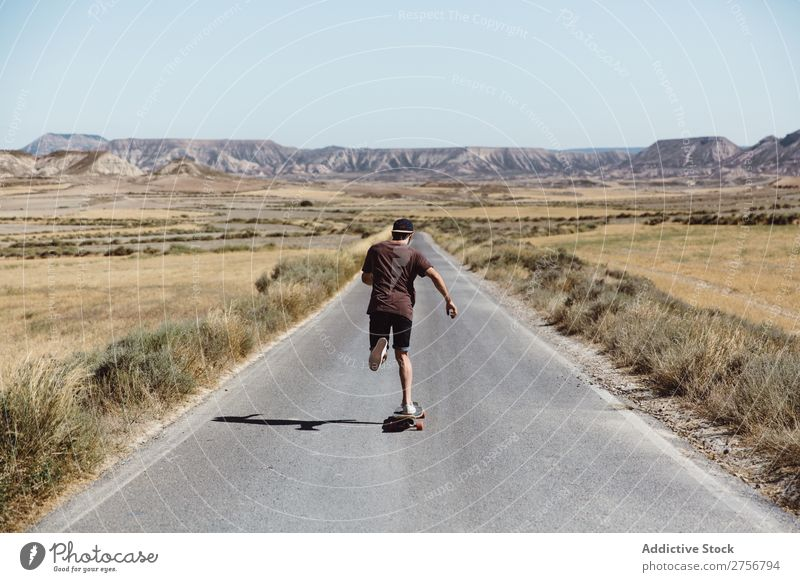 Man riding skateboard on prairie road Skateboard Street Vacation & Travel Lifestyle Human being Adults Nature Adventure Trip Tourist Landscape
