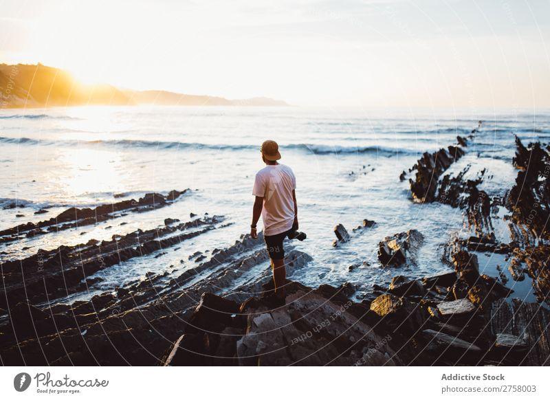 Man with camera on coastal rock Tourist Cliff Ocean Rock shots Camera Photographer Vacation & Travel Tourism Nature Landscape Coast Water Sun Freedom Stone