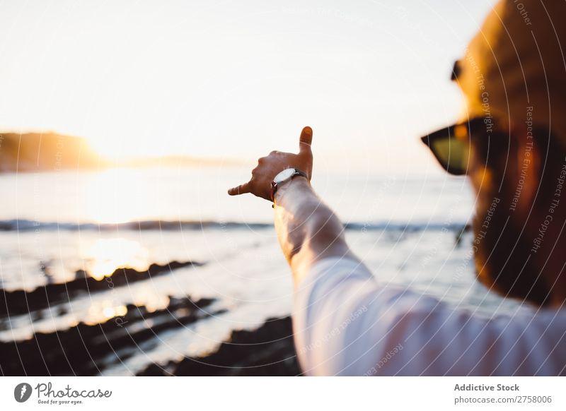 Crop man stretching arm making good gesture Human being Man Hand Ocean Landscape Water Coast Vacation & Travel Nature Summer Sky Rock Island Tourism Sunlight