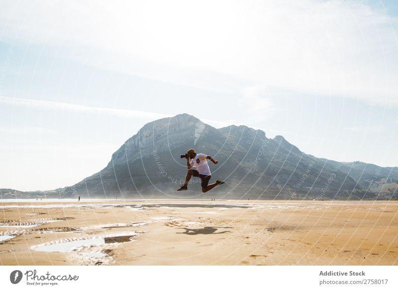 Man jumping on beach Hand Sand Beach Wet Summer Ocean Vacation & Travel Nature Human being Sunlight Leisure and hobbies Relaxation Tropical seaside Sunbeam
