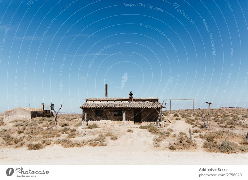 Man sitting on hut roof Hut Roof Desert Vacation & Travel Lifestyle Human being Adults Nature Adventure Trip Tourist Landscape House (Residential Structure)