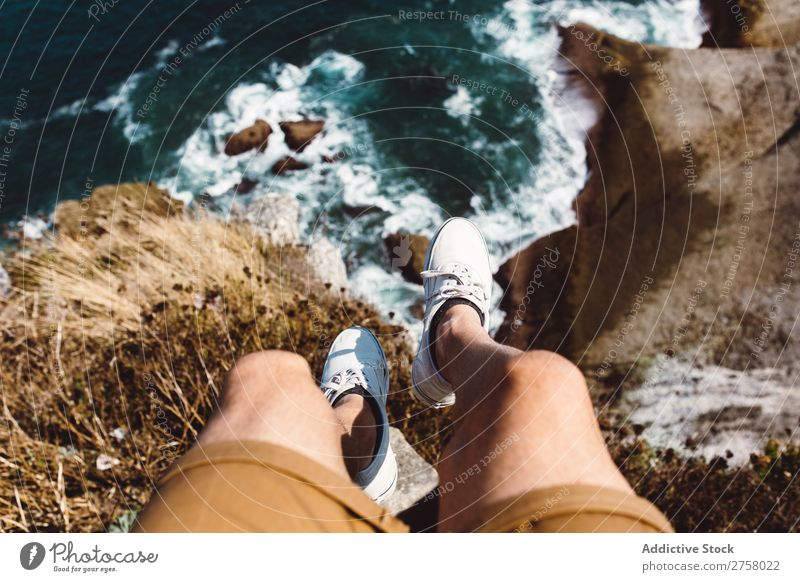 Man sitting on cliff Cliff Vacation & Travel Legs Lifestyle Human being Adults Stone Rock Nature Adventure Freedom traveler Trip Tourist Hot Relaxation Sneakers