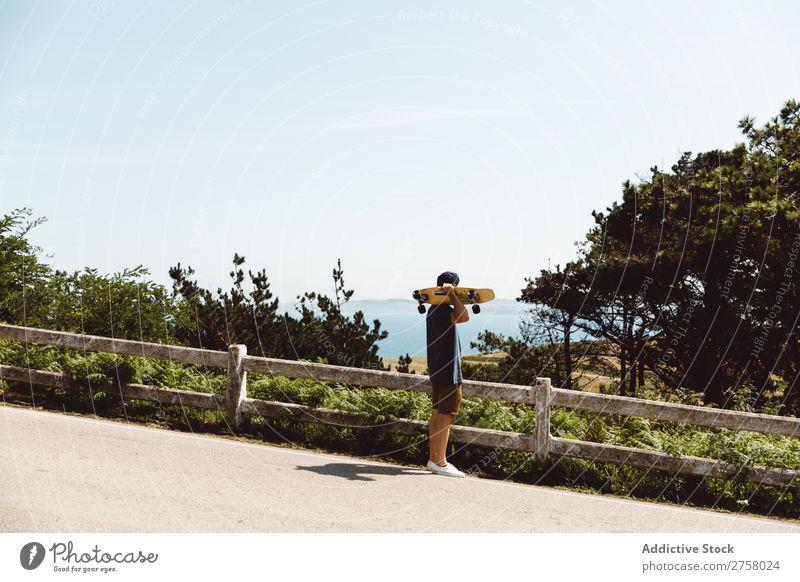 Man holding skateboard near fence skateboarder riding Asphalt seaside Sports Skateboard Lifestyle Ice-skating Skateboarding Ice-skates Extreme Sunbeam Board