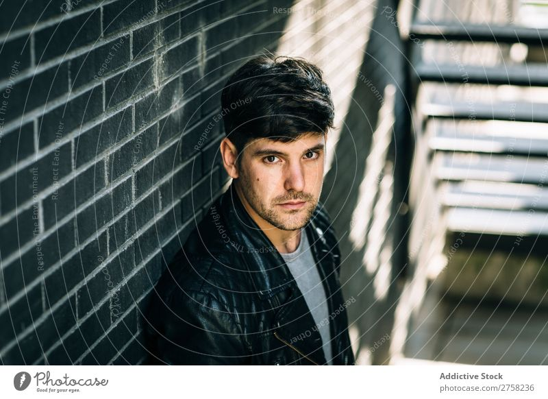 Young pensive man near fire stairs stylish thoughtful looking at camera sitting confident young cool person portrait modern model fashionable male serious