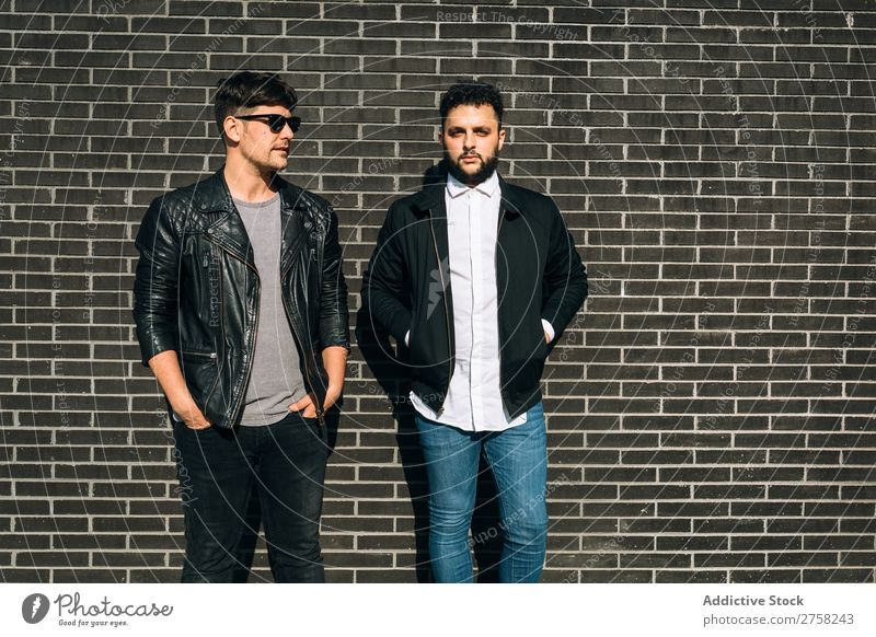 Young homosexual pair looking at camera standing on the background of brick wall. Horizontal outdoors shot. couple gay male love two together lifestyle