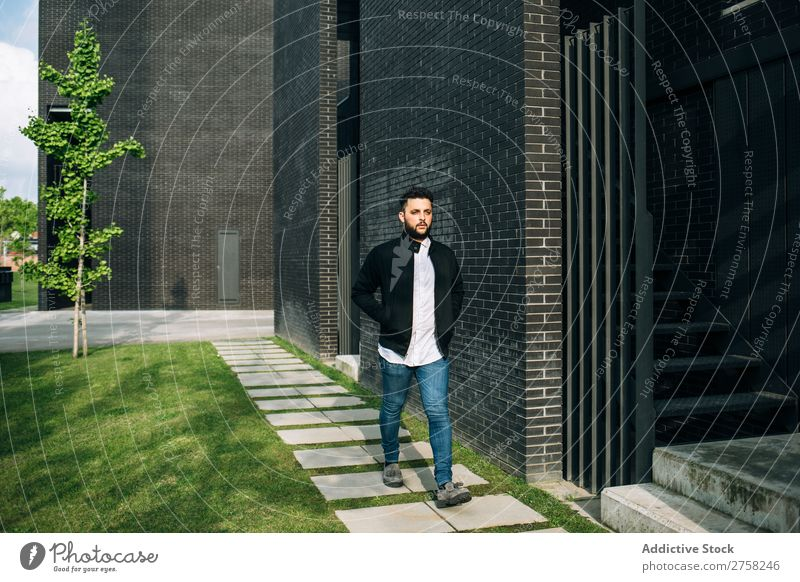 Trendy young man walking in the street looking away thoughtful pensive stylish brick wall standing confident cool person portrait modern model fashionable male