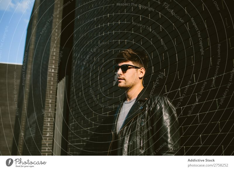 Young handsome man over a dark brick wall serious sunglasses confident young cool person portrait modern model fashionable male casual guy adult caucasian