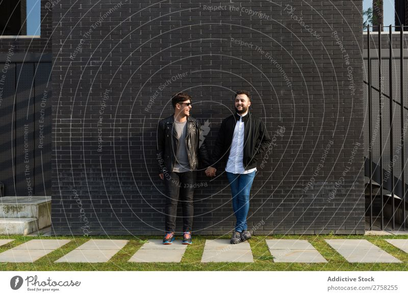 Alternative couple at brick wall standing holding hands looking at camera posing gay homosexual pair male love two together lifestyle relationship young men