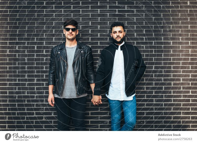 Gay couple holding hands Couple Stand Wall (building) Brick Looking into the camera Posture Homosexual In pairs Man Love 2 Together Lifestyle Relationship
