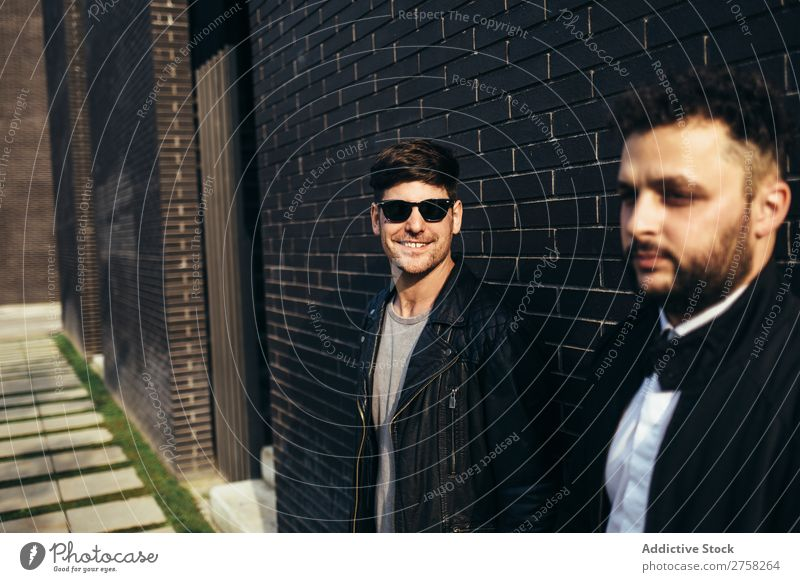 A lovely gay couple holding hands on the background of brick wall. standing looking at camera posing homosexual pair male two together lifestyle relationship