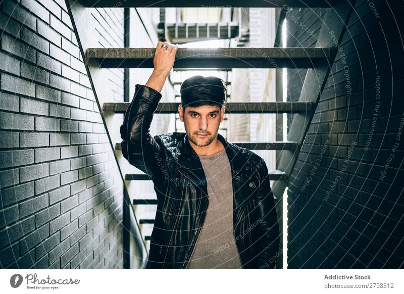 Cool man holding a step Man Self-confident Youth (Young adults) Stairs Jacket Leather Cool (slang) Human being Portrait photograph Modern Model fashionable